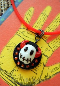 "This free jewelry project by Rings & Things features a stitched devil head lampwork bead as the centerpiece of a mini mosaic. Small beads surround the black white and red focal, which is set into Encapture Artisan Concrete (jewelry grade concrete). The small mosaic is held inside an inexpensive 1"" round bezel cup."