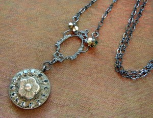 This free jewelry project by Rings & Things uses bezel cups, jewelry grade concrete (EnCapture Artisan Concrete), Gilders Paste, rhinestone chain, vintage inspired filigree, black gunmetal chain and has a delicate flower bead as the center of the mini mosaic.