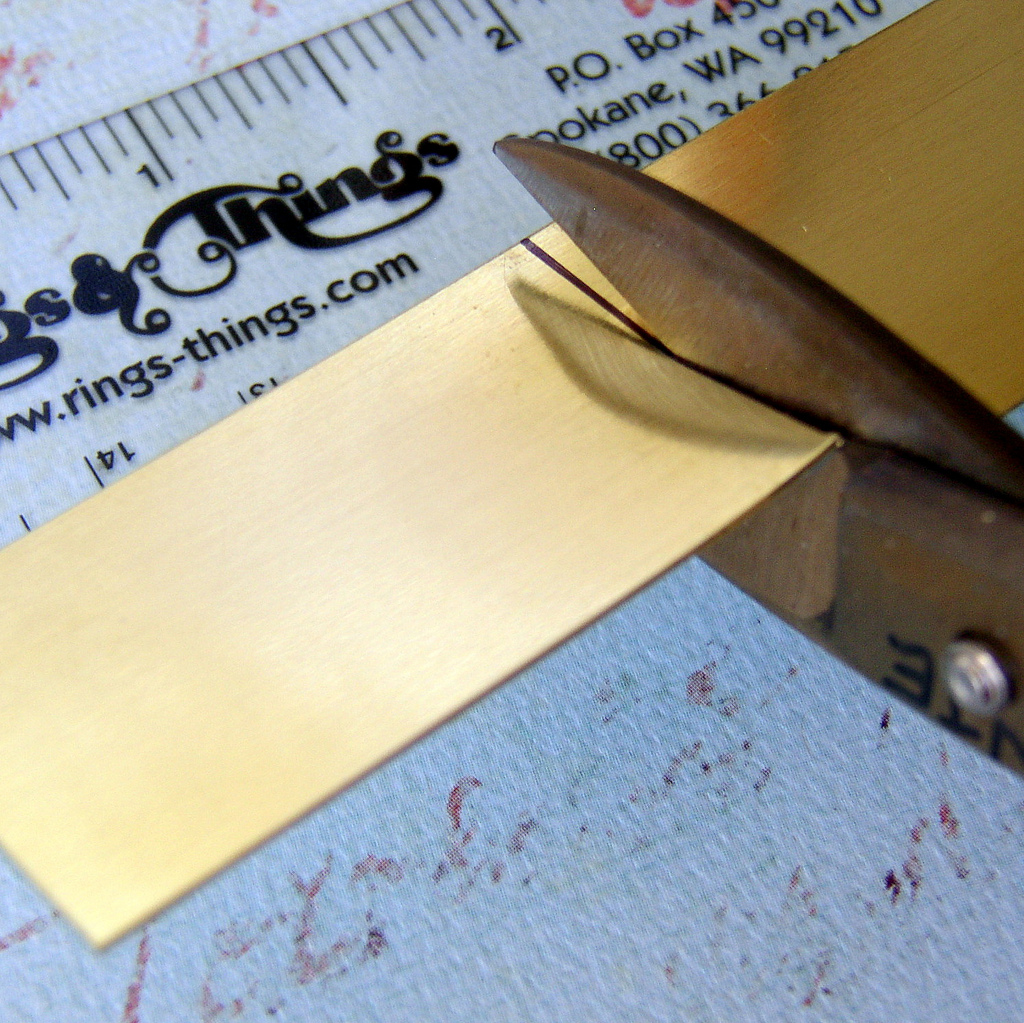 Use metal shears to cut the brass jewelry blank to size.