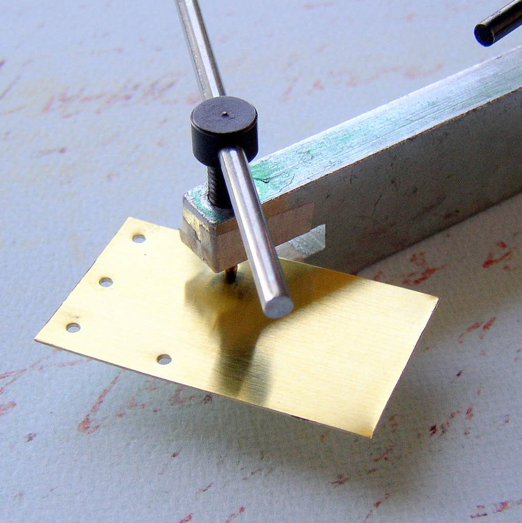 Mark the brass blank for hole placement and use a metal punch to punch the holes.