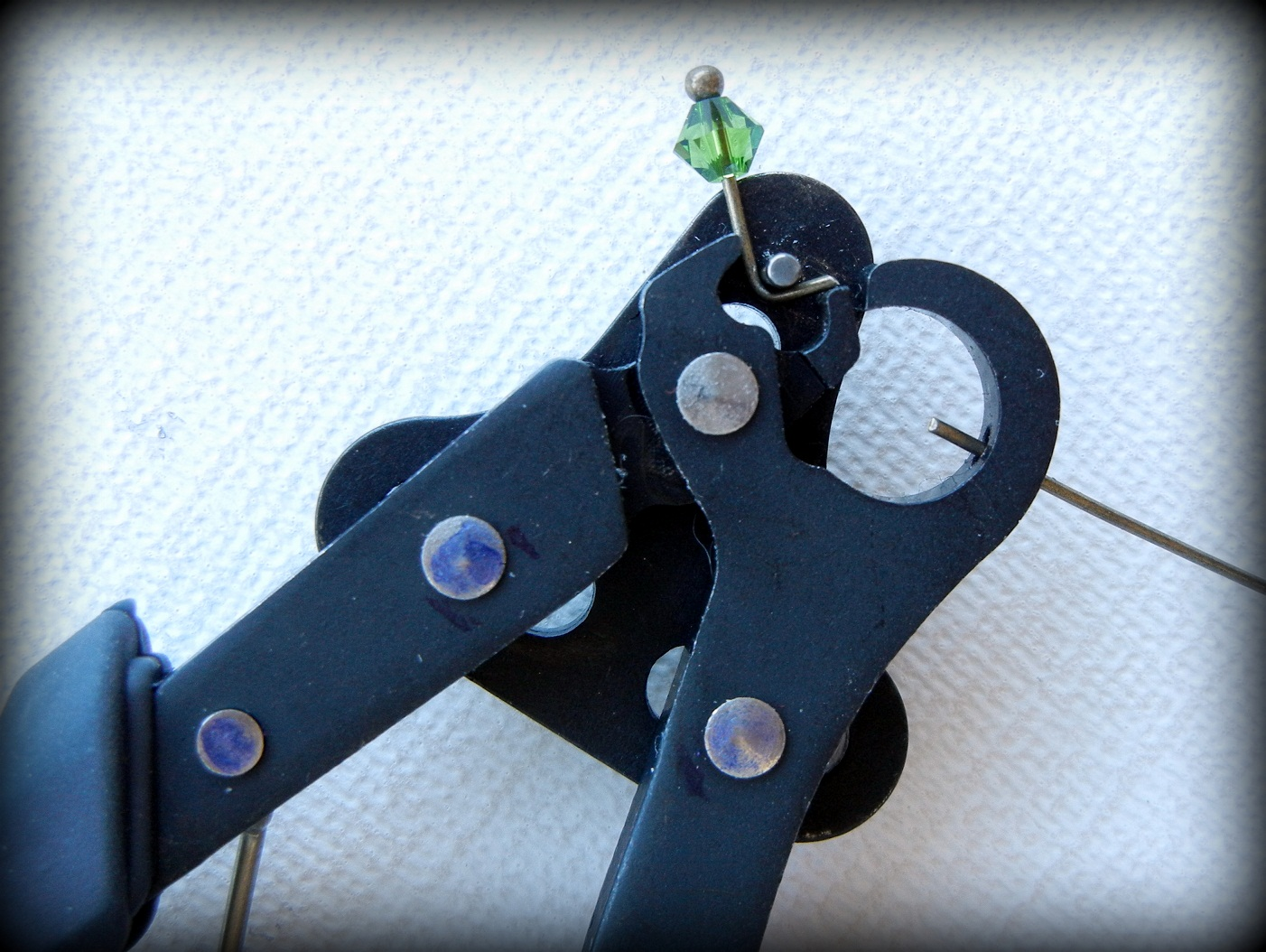 Squeezing the handles of the 1-Step Looper jewelry pliers will cut and shape the wire end.