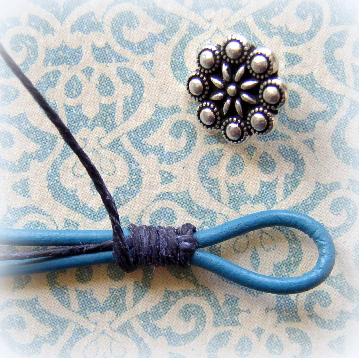 Lashing the button loop securely to make a Rhinestone and Leather wrap Bracelet