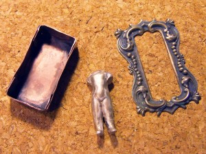 Antique and patina the frozen charlotte doll, the ornate brass frame and the brass metal box to create the reliquary.