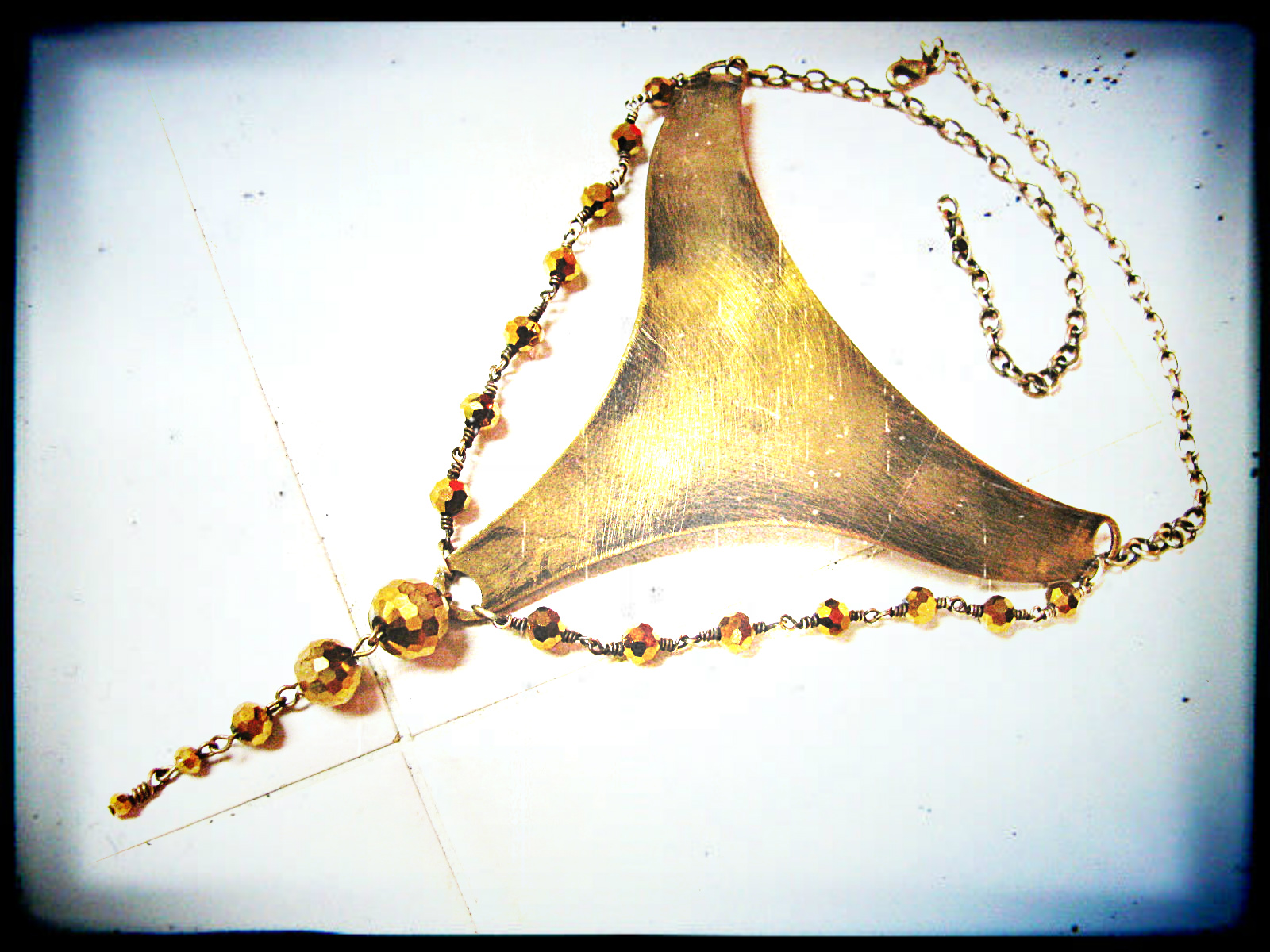 The necklace made for [...]. I antiqued and sanded this piece of raw brass and then added golden sparkly glass to give it some pizzazz..