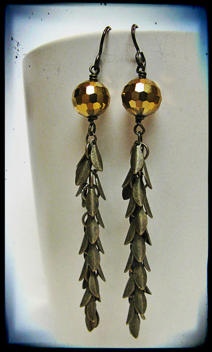 Close-up of Mandi's earrings featuring gold sparkly glass and brass leaf charm chain.