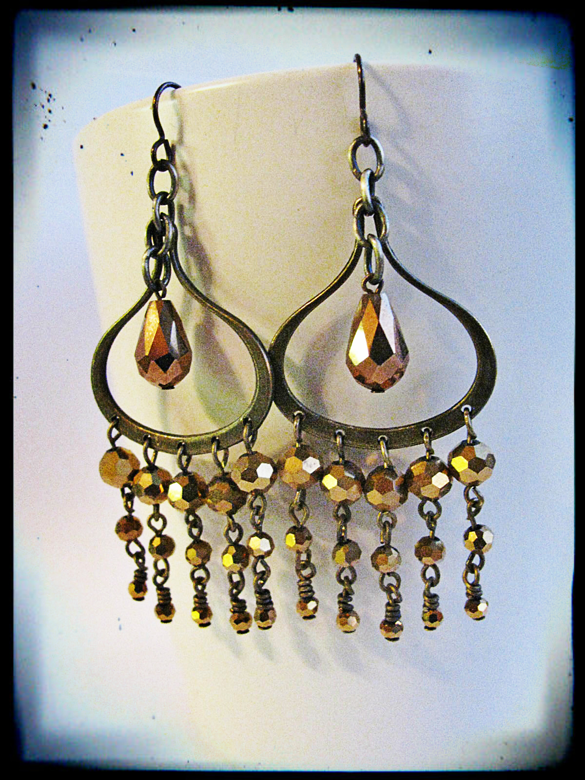 Close-up of the earrings. Onion-shaped chandelier findings with graduated gold sparkly glass.