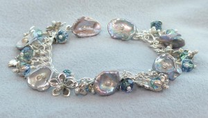 Moondance, a free DIY bracelet project, using sterling silver, keishi pearls and faceted Swarovski crystal beads was designed by Sondra Barrington of Rings & Things.  This handmade jewelry design features flower, petal and leaf bead caps made of sterling silver as well as center drilled keishi pearls in a beautiful shimmering silvery gray/light blue color. Free instructions for creating this handmade, heirloom quality charm bracelet at www.rings-things.com.