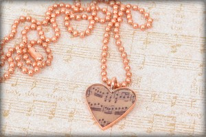 A heart-shaped bezel and Piddix image of music notes is featured in this cast resin necklace: Music Lover Necklace by Valorie Nygaard-Pouzar of www.rings-things.com