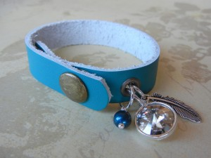 Blue Leather Cuff Bracelet with a SWAROVSKI ELEMENTS crystal rivoli stone in a 1-loop rivoli setting, a TierraCast® feather charm and a blue pearl dangle.