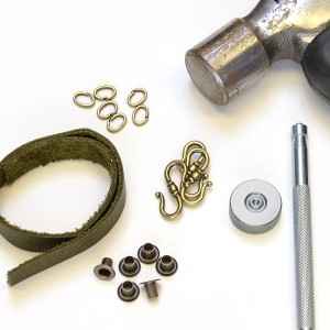 Gather the necessary supplies (leather strip, eyelets, locking jump ring, S clasp, eyelet setter, hammer, leather hole punch).