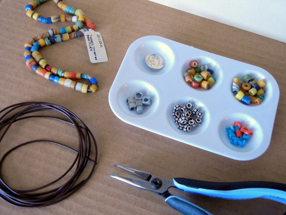 You will need Greek leather, glass trade beads, metal beads, and a metal button to make a trade bead and leather bracelet.