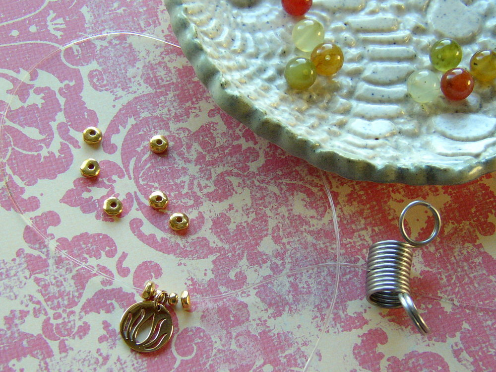 To make a yoga bracelet, add a charm and gold plated beads to the center of the Stretch Magic cord.