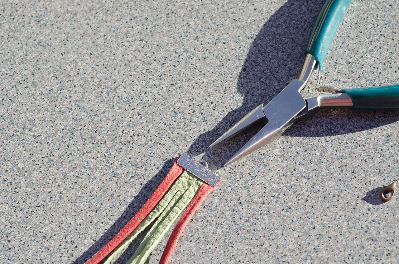 Slive your cord end on and using your chain nose pliers crimp the end.