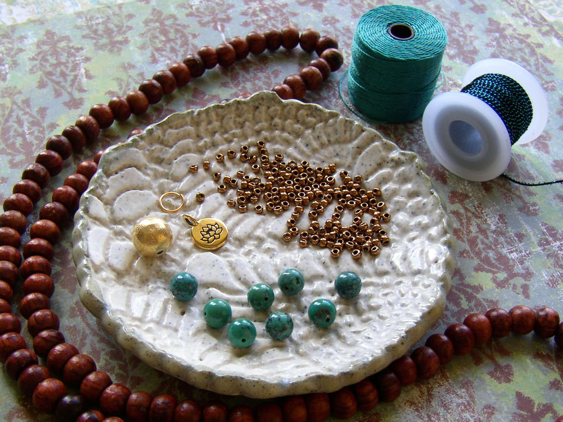 Supplies needed to make a personal Mala necklace include rosewood beads and a lotus charm