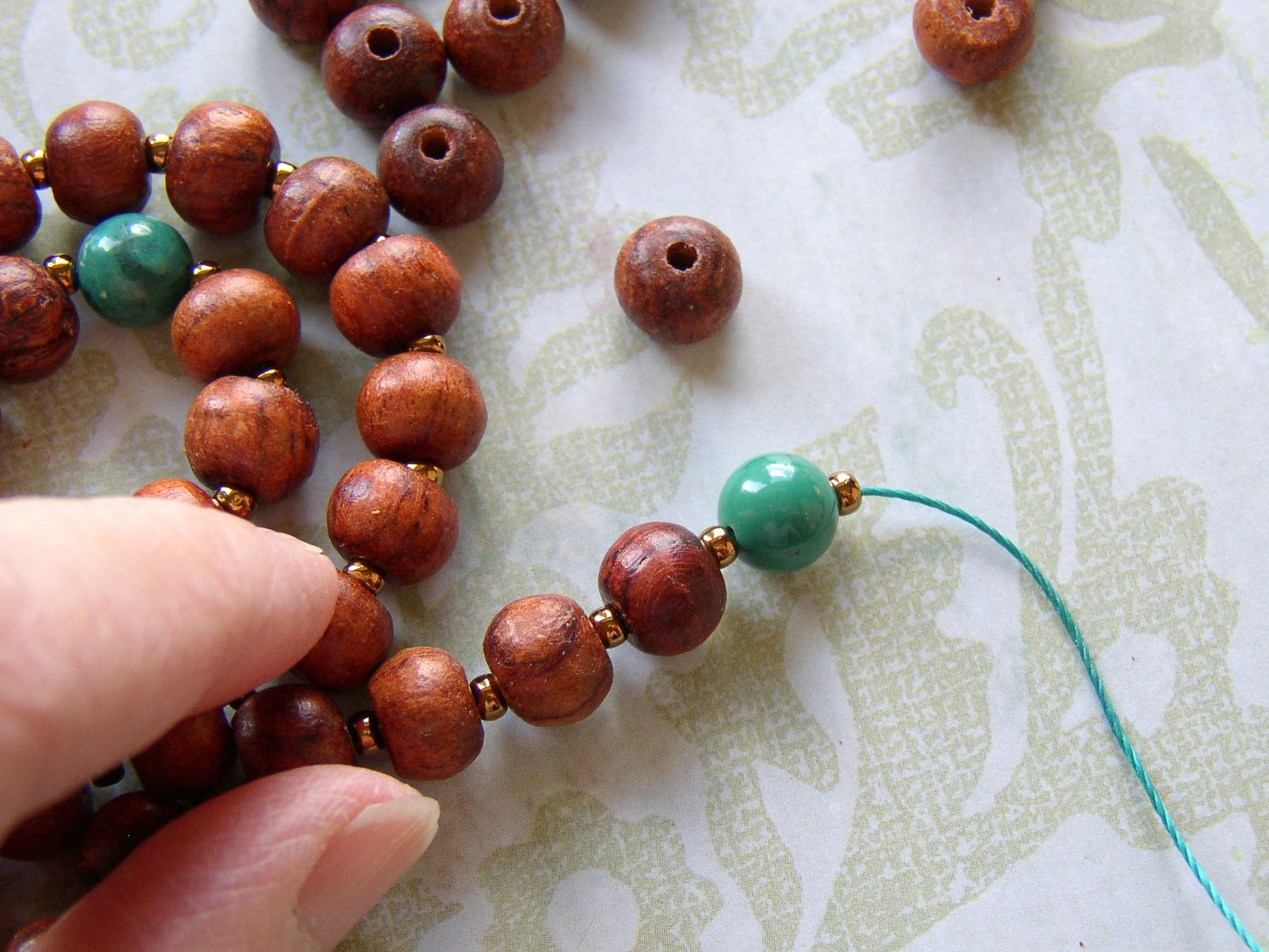 Finish stringing the handmade mala and add a size 8 seed bead.